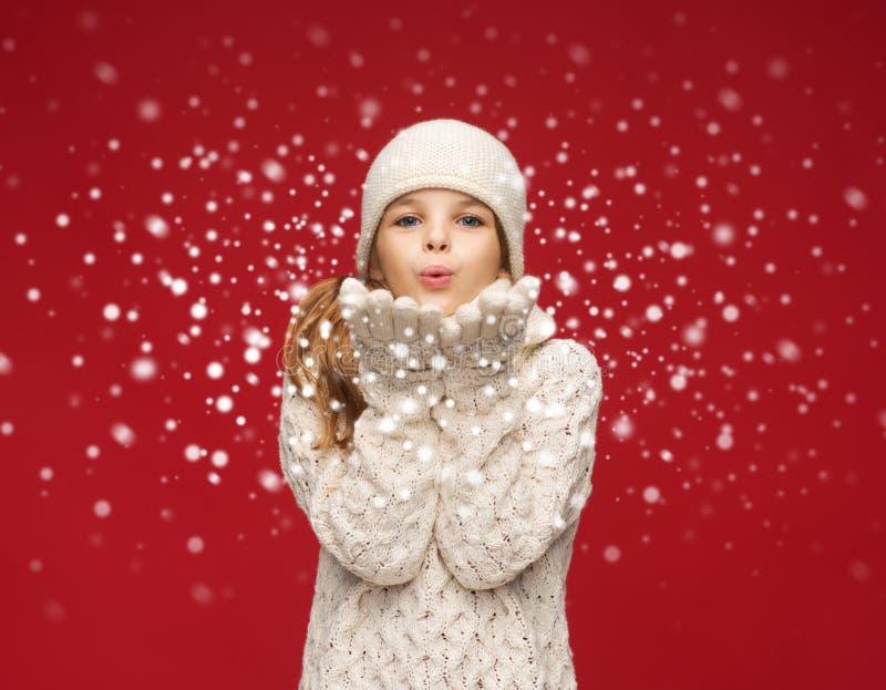 愉快的女孩在冬天给吹在棕榈穿衣 免版税图库摄影