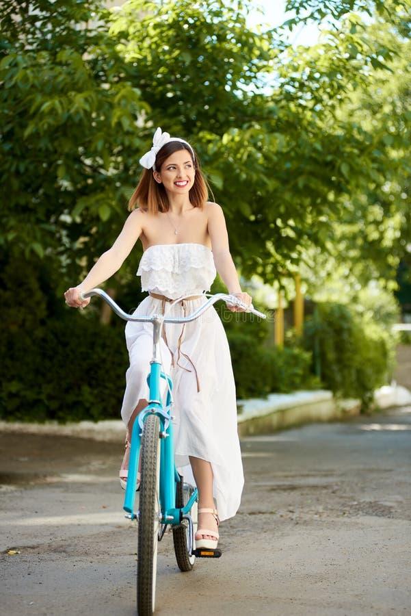 愉快的女孩在减速火箭的自行车乘坐反对背景绿色种植 库存图片