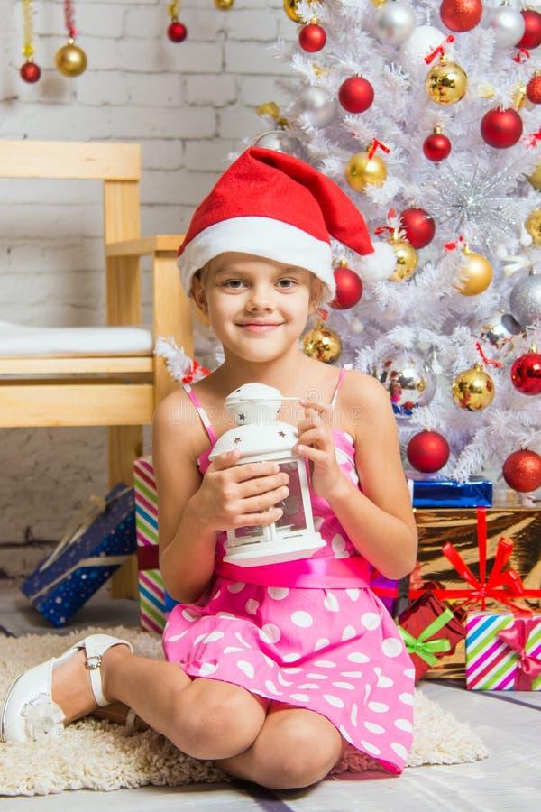 愉快的女孩在手上的举一个蜡烛坐在新年内部人字形 免版税图库摄影