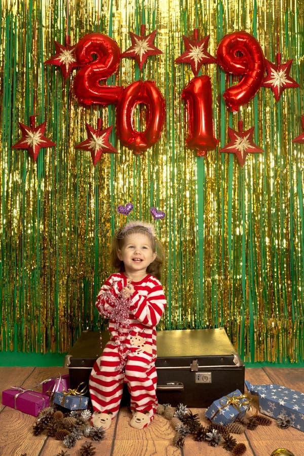 愉快的女孩坐减速火箭的手提箱圣诞节背景 库存图片