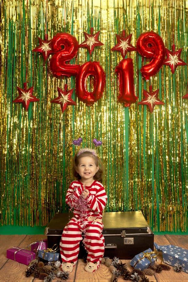 愉快的女孩坐减速火箭的手提箱圣诞节背景 免版税库存照片