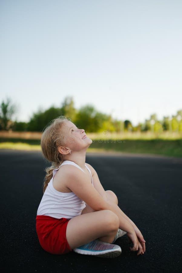 愉快的女孩坐地板户外 免版税图库摄影