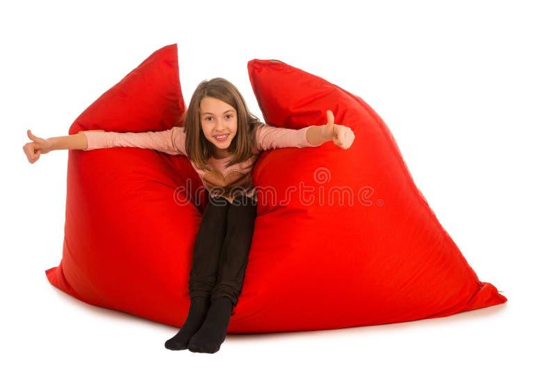 愉快的女孩坐客厅或其他的红色装豆子小布袋沙发 免版税库存照片