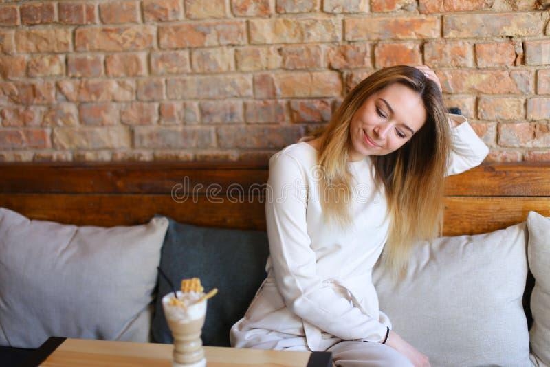 愉快的女孩坐木椅子在与杯子的桌附近热奶咖啡 免版税库存照片