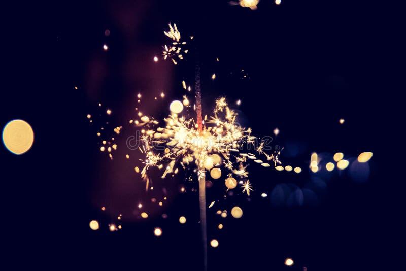 愉快的女孩拿着一个闪烁发光物在圣诞节打过工 免版税库存照片