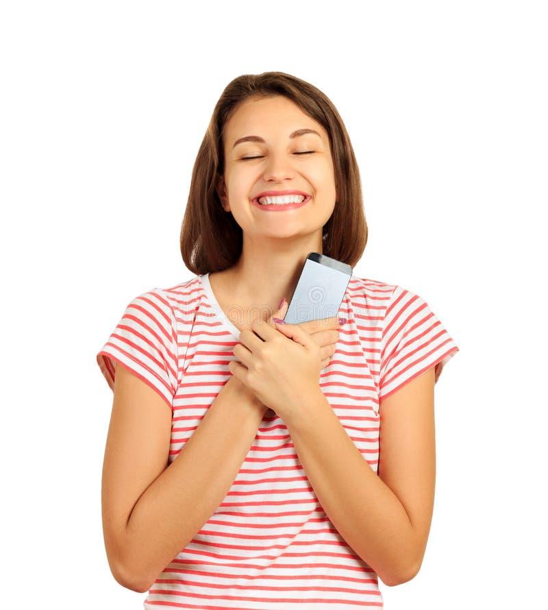 愉快的女孩按了电话用喜悦手对她的胸口和梦想从消息的 在白色backgr隔绝的情感女孩 免版税库存照片