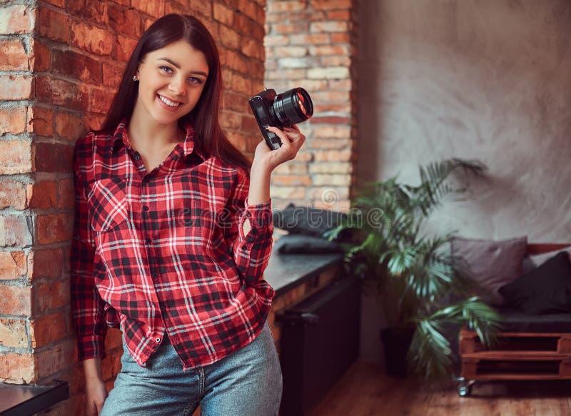 愉快的女孩摄影师在拿着照相机和看照相机的格子花呢上衣和牛仔裤穿戴了,当倾斜时 图库摄影