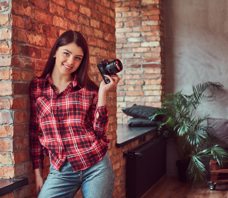 愉快的女孩摄影师在拿着照相机和看照相机的格子花呢上衣和牛仔裤穿戴了,当倾斜时 库存图片