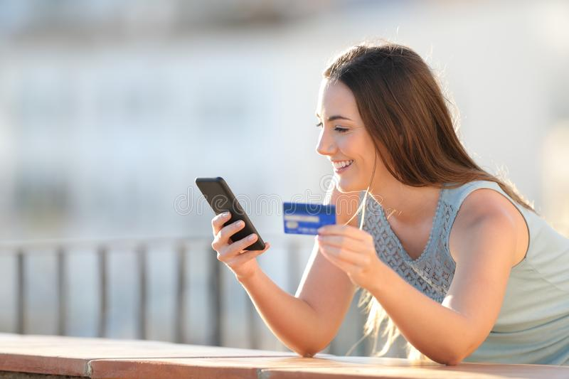 愉快的女孩支付与信用卡和电话 免版税库存图片