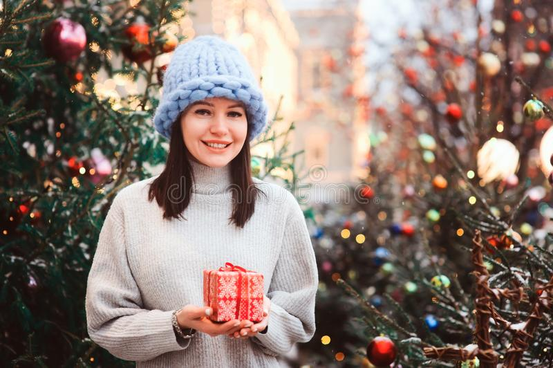 愉快的女孩新年画象特大大块编织帽子的在圣诞节购物在城市假日市场上 库存照片