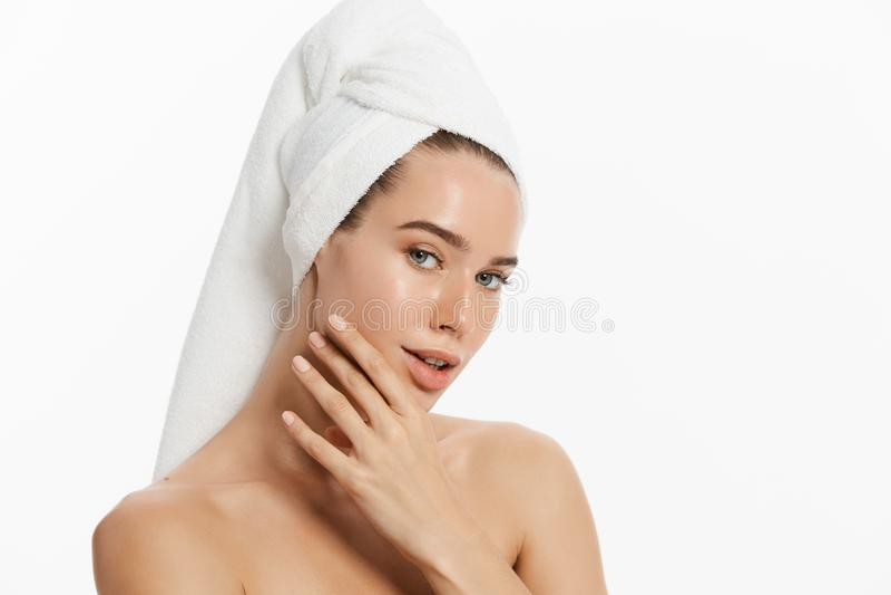 愉快的女孩有干净的皮肤的和有在她的顶头洗涤面孔的一块白色毛巾的 库存照片