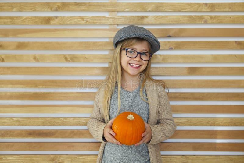 愉快的女孩用由木墙壁背景的秋天南瓜 库存照片