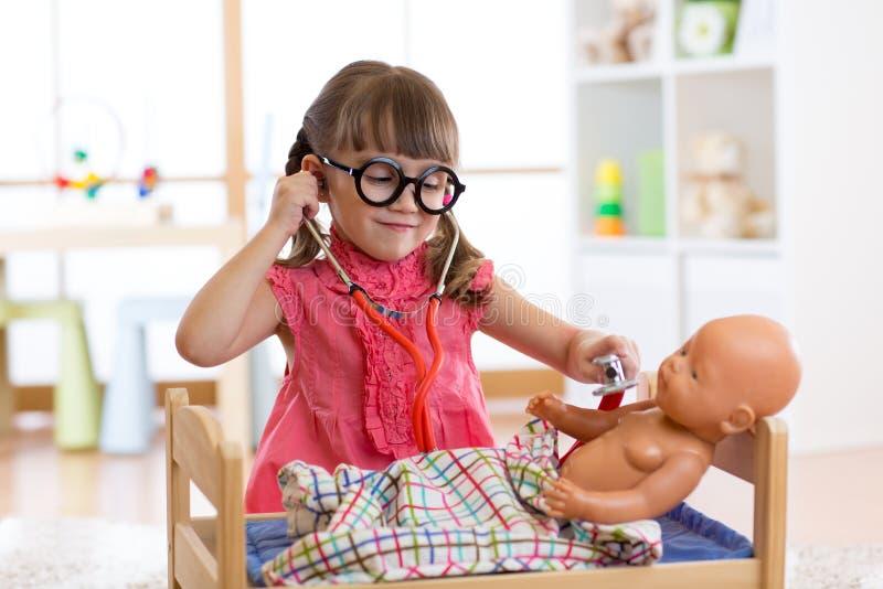 愉快的女孩画象与玻璃的3岁在家或有玩偶的托儿所室,扮演医生 免版税图库摄影