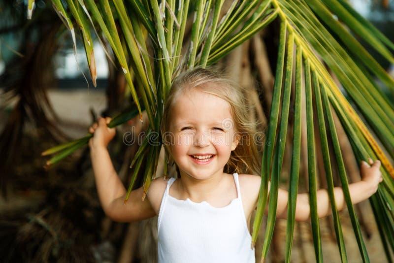愉快的女孩画象有棕榈叶的 暑假概念,热带震动 孩子微笑 免版税库存图片