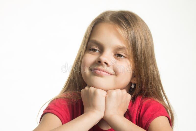 愉快的女孩画象,她在她的拳头投入了她的头和神色到左边 库存图片
