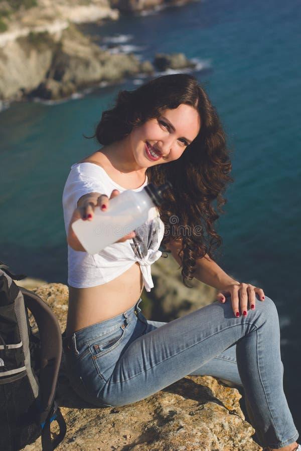 愉快的女孩背包徒步旅行者坐在海的岩石峰顶 库存图片