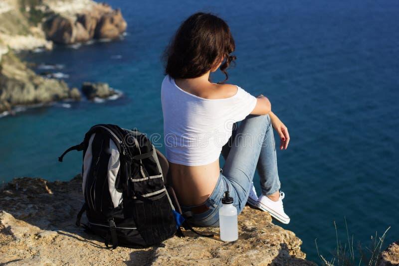愉快的女孩背包徒步旅行者坐在海的岩石峰顶 图库摄影