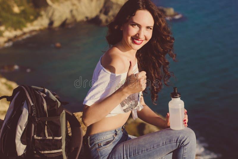 愉快的女孩背包徒步旅行者坐在海视图的岩石 免版税库存图片