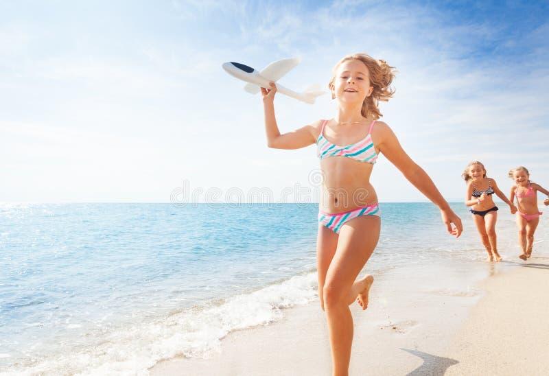 愉快的女孩跑与在海滩的飞机模型 免版税图库摄影