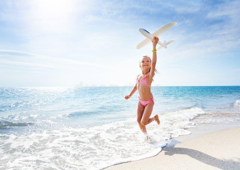 愉快的女孩跑在海滩并且拿着玩具飞机 免版税库存图片