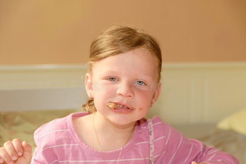 愉快的女孩食用一顿快餐在厨房 一个逗人喜爱的小女孩吃在面包spred的巧克力奶油 一个小女孩与 免版税库存照片