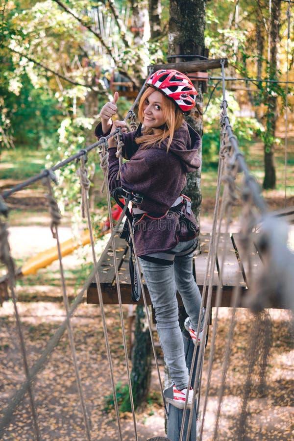 愉快的女孩,妇女,上升的齿轮在冒险公园参与攀岩在绳索路,树木园,保险, 免版税库存图片