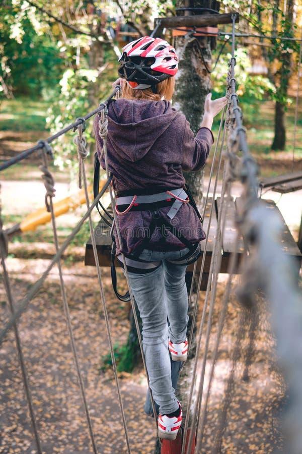 愉快的女孩,妇女,上升的齿轮在冒险公园参与攀岩在绳索路,树木园,保险, 免版税图库摄影