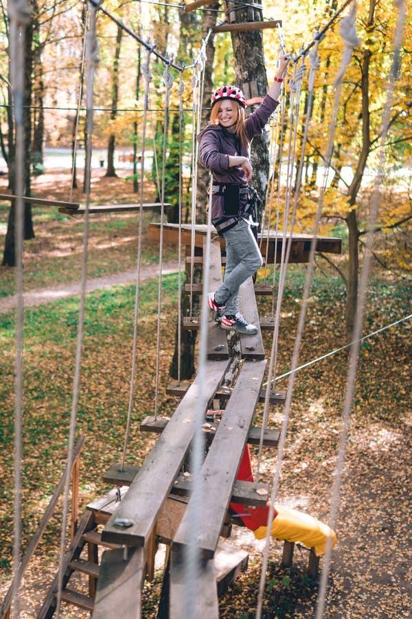 愉快的女孩,妇女,上升的齿轮在冒险公园参与攀岩在绳索路,树木园,保险, 免版税库存照片