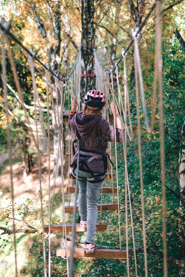 愉快的女孩,妇女,上升的齿轮在冒险公园参与攀岩在绳索路,树木园,保险, 库存图片