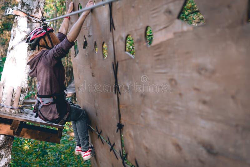 愉快的女孩,妇女,上升的齿轮在冒险公园参与攀岩或通过在绳索路,树木园的障碍, 免版税库存照片