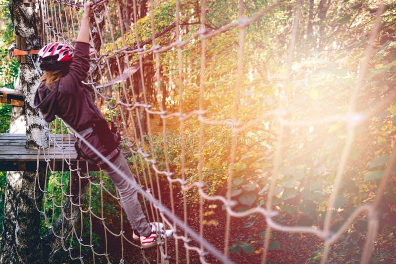 愉快的女孩,妇女,上升的齿轮在冒险公园参与攀岩或通过在绳索路,树木园的障碍, 库存图片