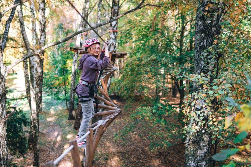 愉快的女孩,妇女,在冒险的上升的齿轮,绳索路,保险,吸引力,游乐场,活跃休闲,秋天 免版税图库摄影