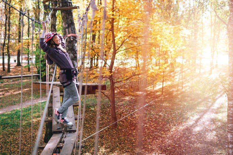 愉快的女孩,妇女,在冒险的上升的齿轮,绳索路,保险,吸引力,游乐场,活跃休闲,秋天 库存照片