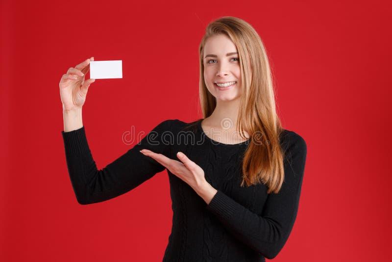 愉快的女孩,显示一空白名片和微笑 库存图片