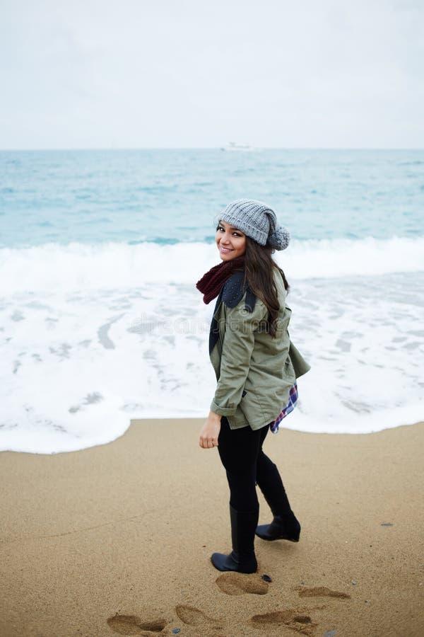 愉快的女孩去水接触它在一凉快的秋天天 免版税图库摄影