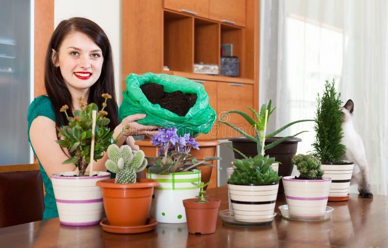 愉快的女孩移植的盆的花 图库摄影