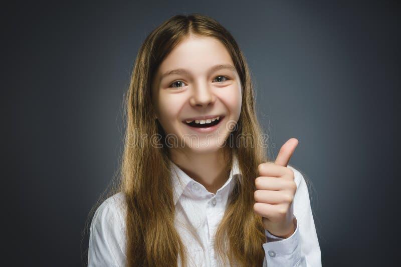 愉快的女孩 特写镜头画象英俊青少年在偶然在灰色背景的衬衣微笑的展示赞许 免版税图库摄影