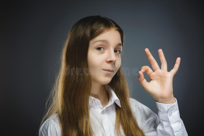 愉快的女孩 特写镜头画象英俊青少年在偶然在灰色背景的衬衣微笑的展示Ok孤立 免版税库存图片