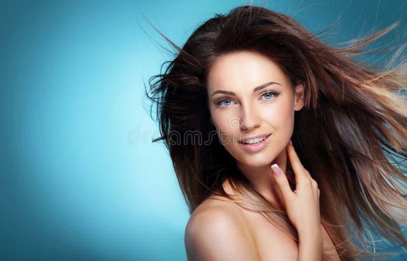 愉快的女孩画象有长的黑暗的吹的头发的反对蓝色 库存图片