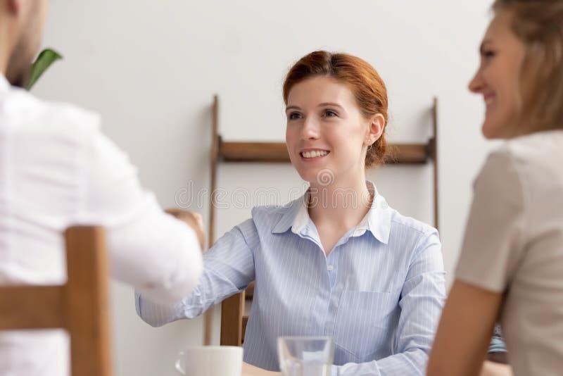 愉快的女实业家握手伙伴做与客户的成交在见面 库存照片