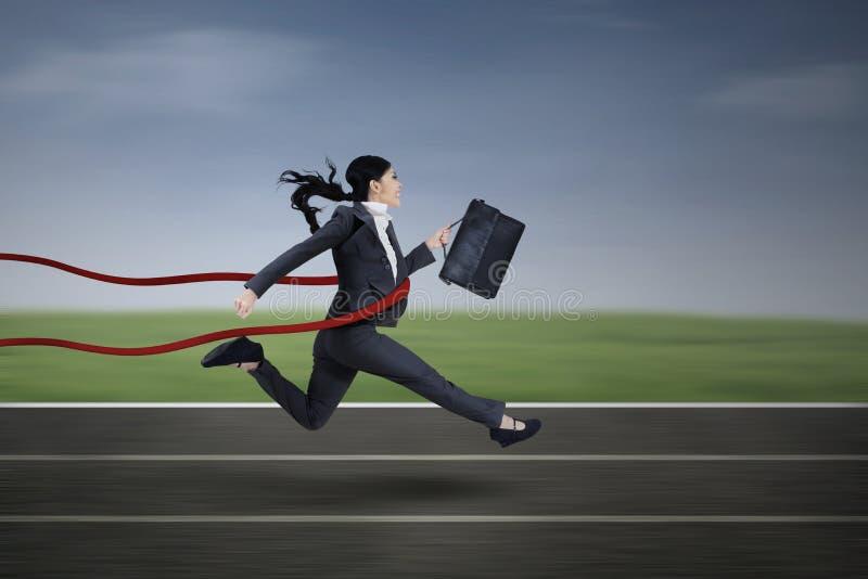 愉快的女实业家横穿终点线 免版税库存图片
