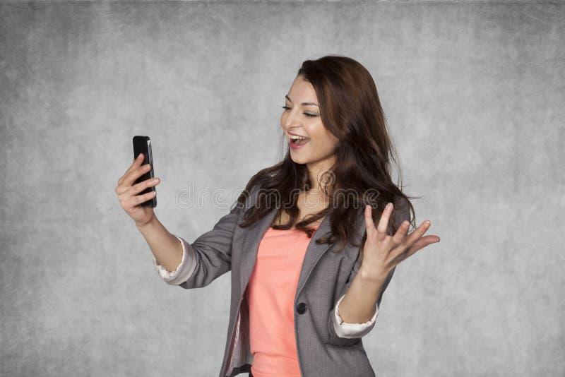 愉快的女实业家读书电子邮件 库存图片