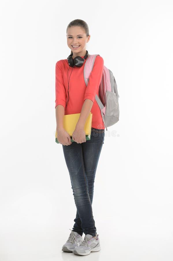 愉快的女小学生。举行与书包的愉快的少年女小学生 免版税库存照片