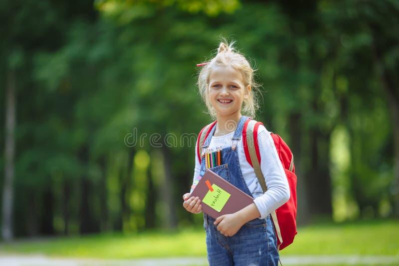 愉快的女小学生画象有书和红色背包的 r 图库摄影