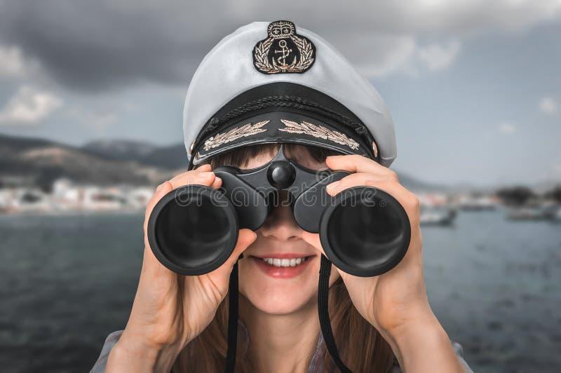 愉快的女性上尉通过看双筒望远镜 库存照片