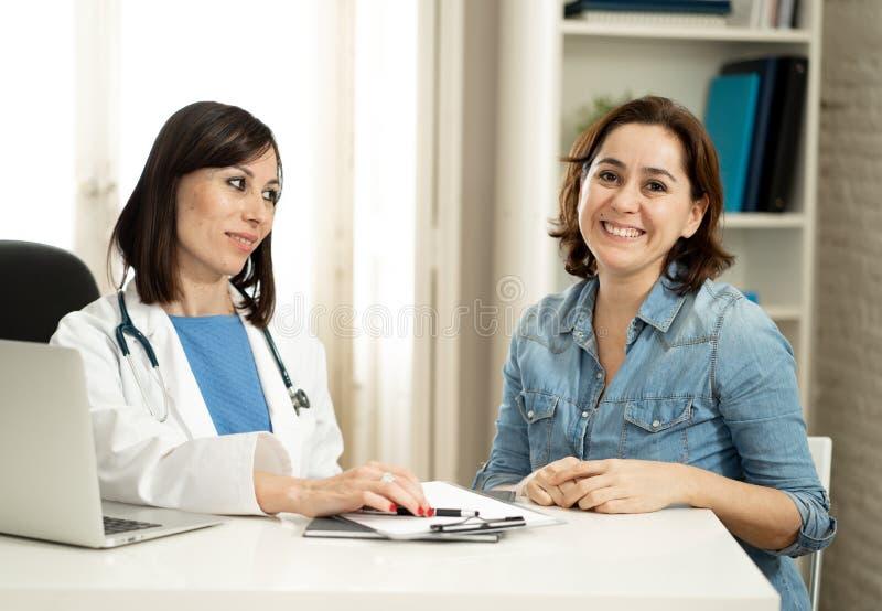 愉快的女性医生和年轻人满意的微笑的患者有咨询在诊所办公室 免版税库存照片