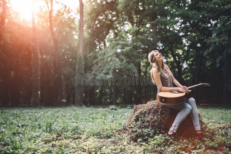愉快的女性吉他演奏员 图库摄影