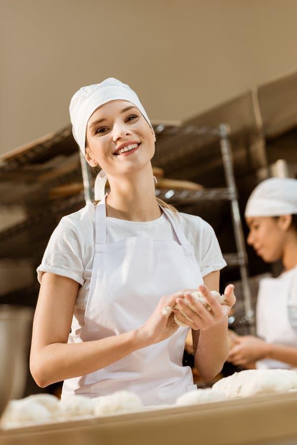 愉快的女性在烘烤的制造的面包师揉的面团,当她同事工作被弄脏时的 库存照片