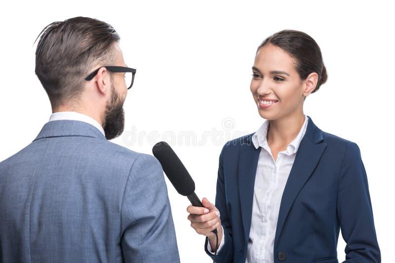 愉快的女性在衣服的新闻工作者采访的商人, 图库摄影