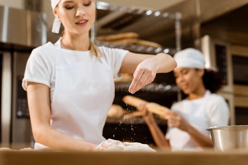 愉快的女性对此在烘烤的制造,当她同事工作被弄脏时的面包师揉的面团和倾吐的面粉 免版税库存图片
